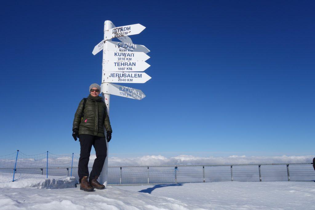 Winters geklede persoon staat in de sneeuw naast een wegwijzer op de berg Olympos, Turkije