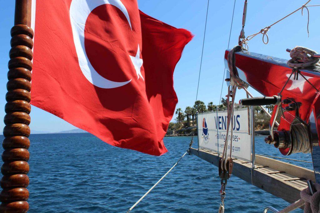 Een wapperende Turkse vlag op het achterdek van een zeilschip