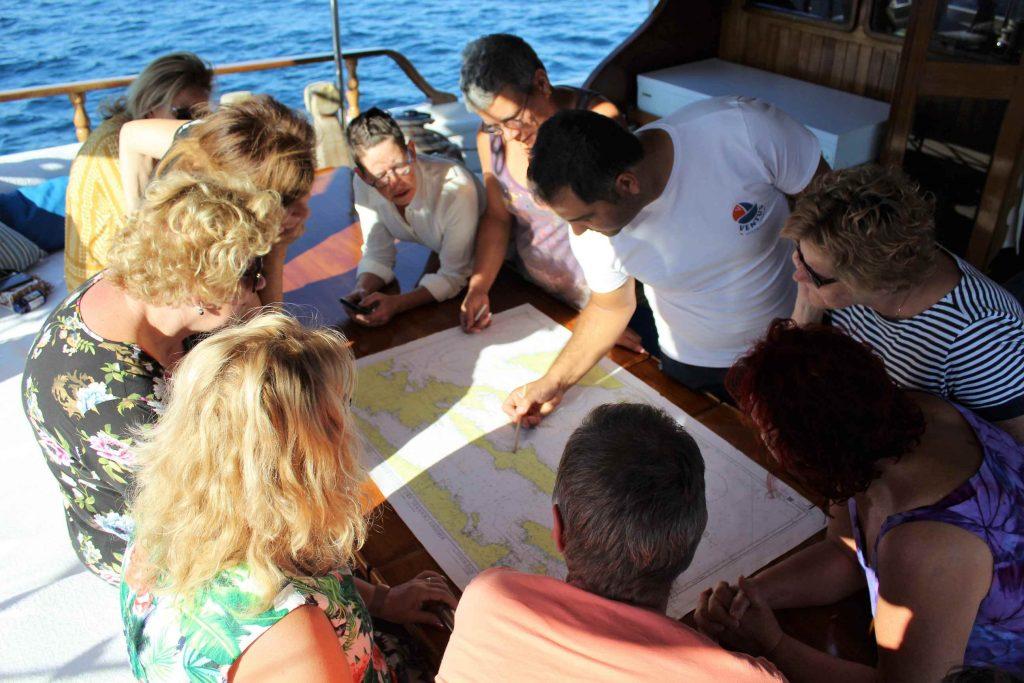 Briefing voor zeilen door kapitein met Turkse zeekaart en passagiers rond de tafel waar de kaart op ligt