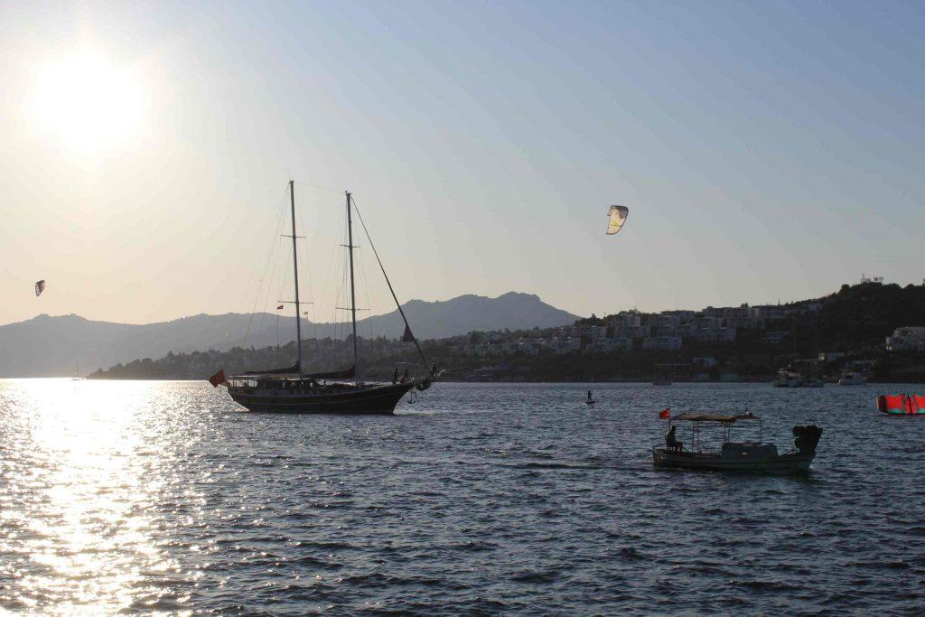Turks zeiljacht komt Bitez binnenvaren met kitesurfers eromheen