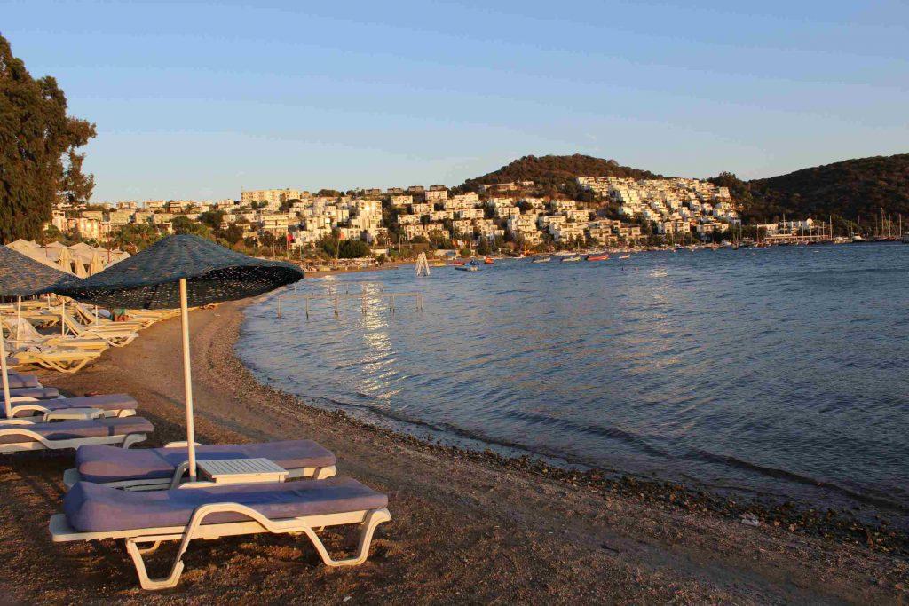 Strand van Bitez in Turkije met zonnebedjes en rotan parasols en in de verte allemaal witte huisjes