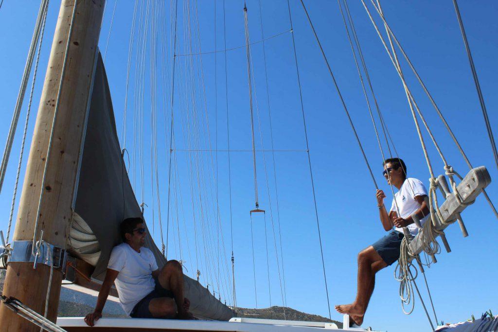 Bemanningsleden van zeilschip Borina 1 wachten zittend op de kajuit tot ze de zeilen kunnen hijsen