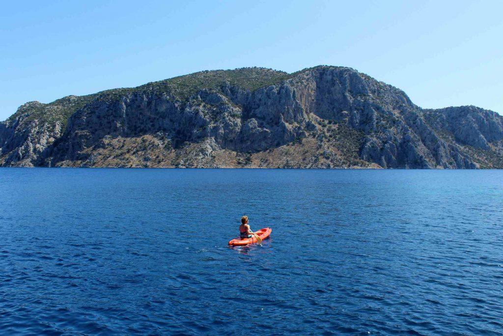 Iemand in een oranje kano peddelt door een baai in de Turkse Egeïsche Zee