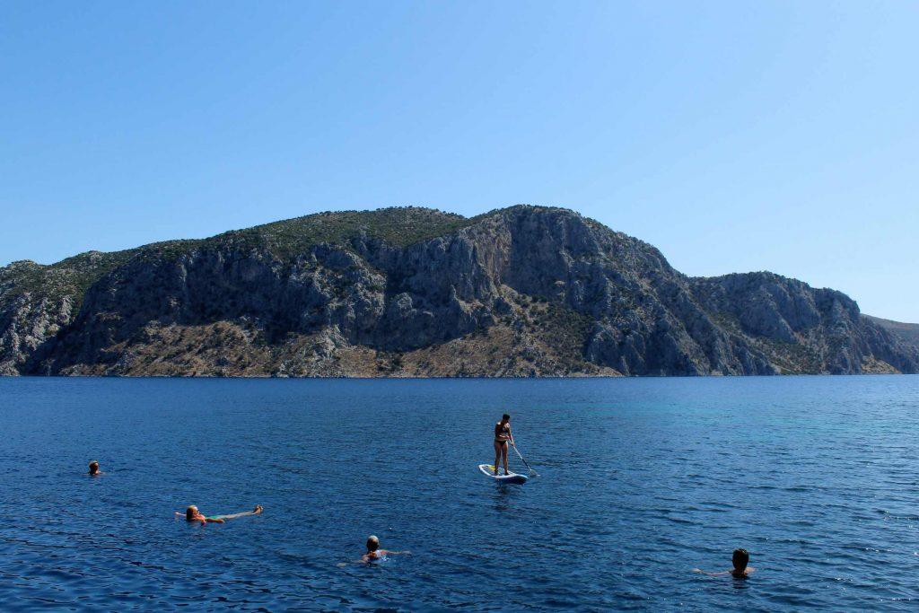 Iemand op een supboard met vier zwemmers eromheen in een Turkse baai