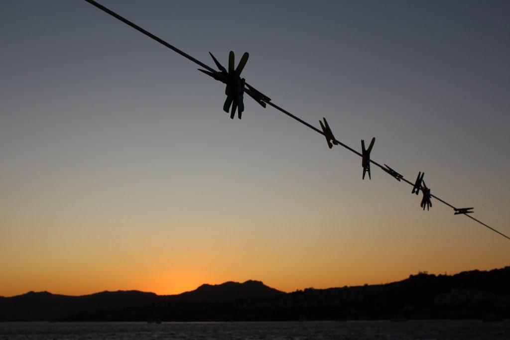 Wasknijpers aan de waslijn aan boord van een zeilschip terwijl de zon achter de bergen zakt