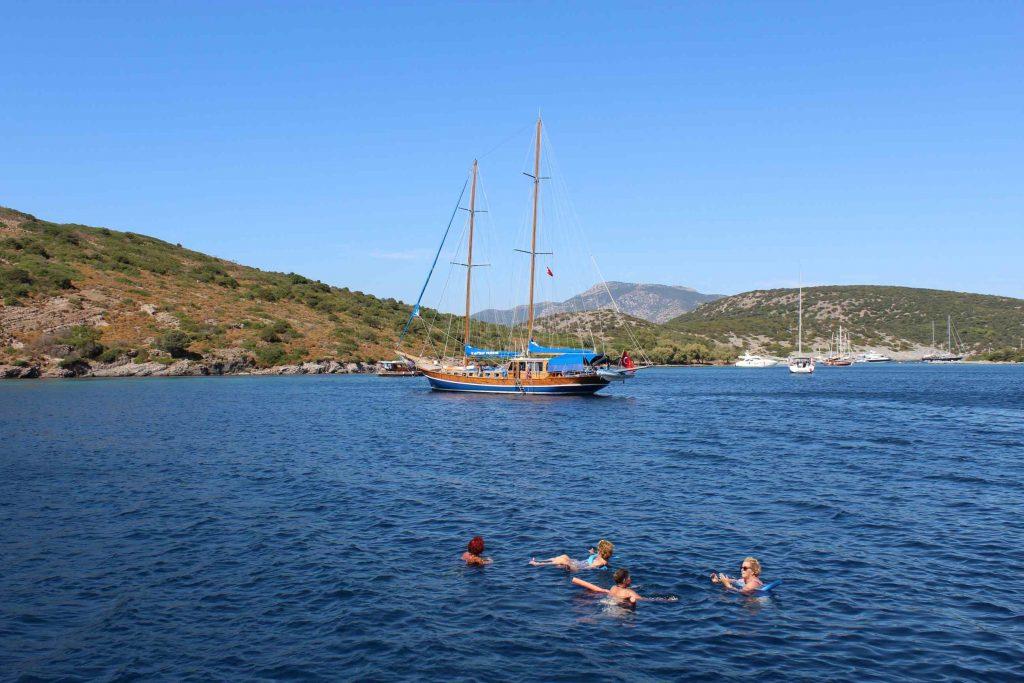 Vier dames zwemmen in zee met op de achtergrond een Turks zeiljacht