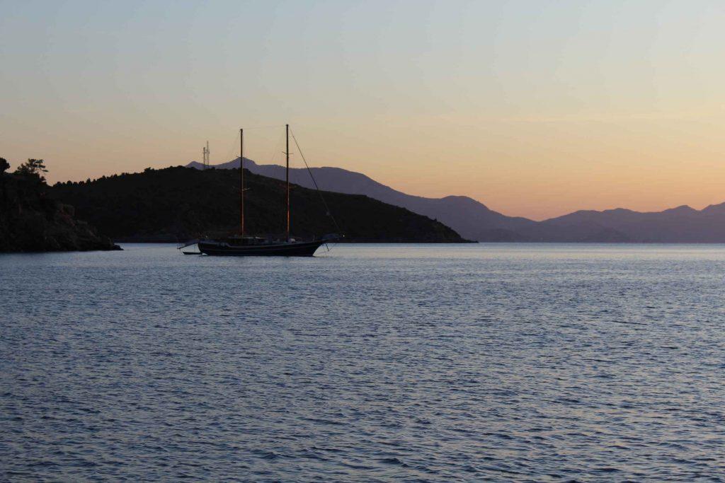 Turks zeiljacht in een baai bij zonsondergang