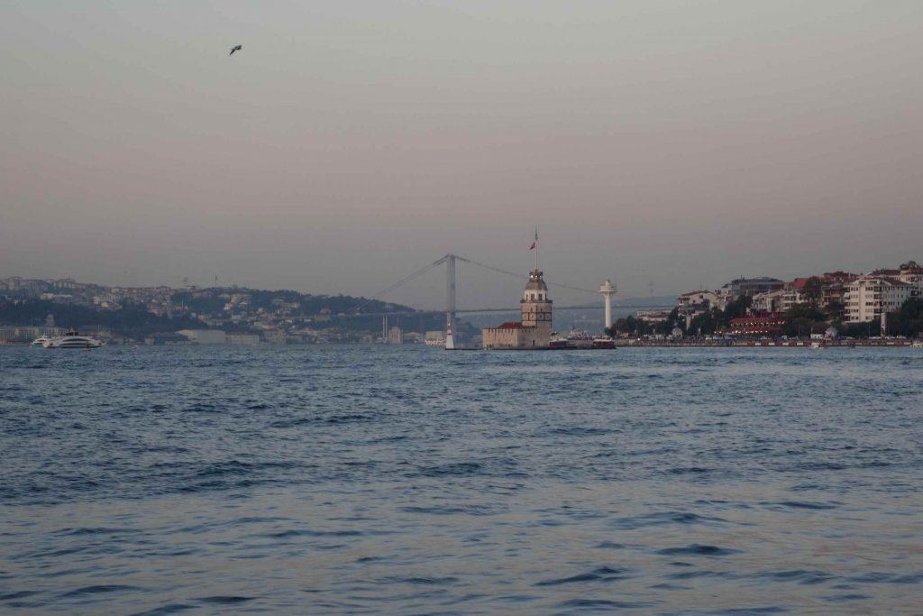 De Maiden's Tower, een wit torentje middenin de Bosporus bij Istanbul met op de achtergrond een hangbrug
