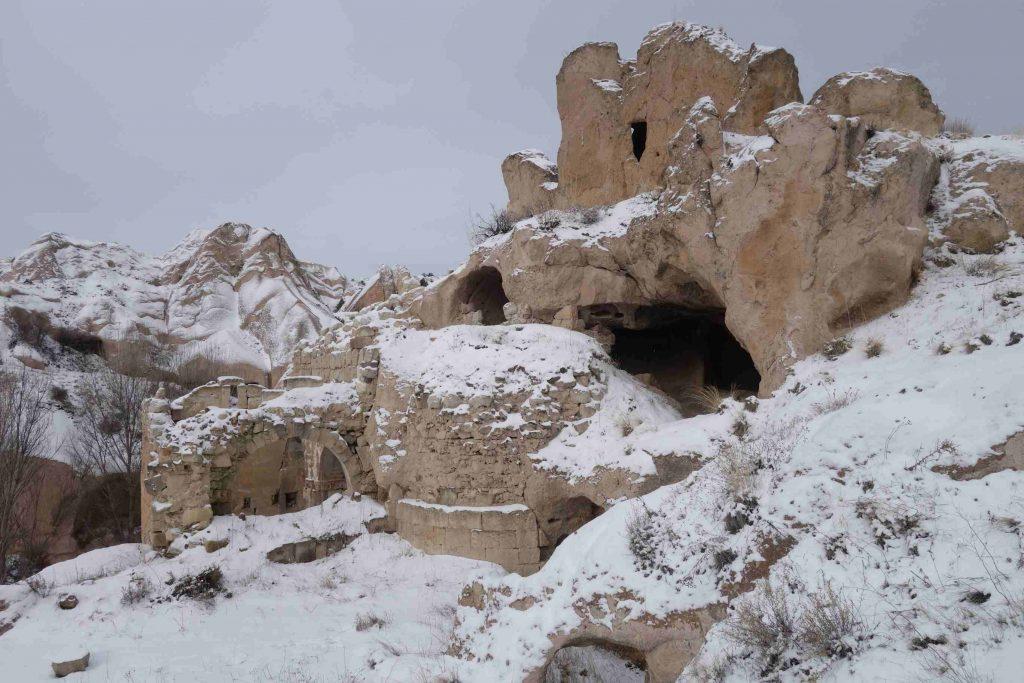 In de rotsen uitgehakte rotskerk in besneeuwd landschap in Cappadocië, turkije